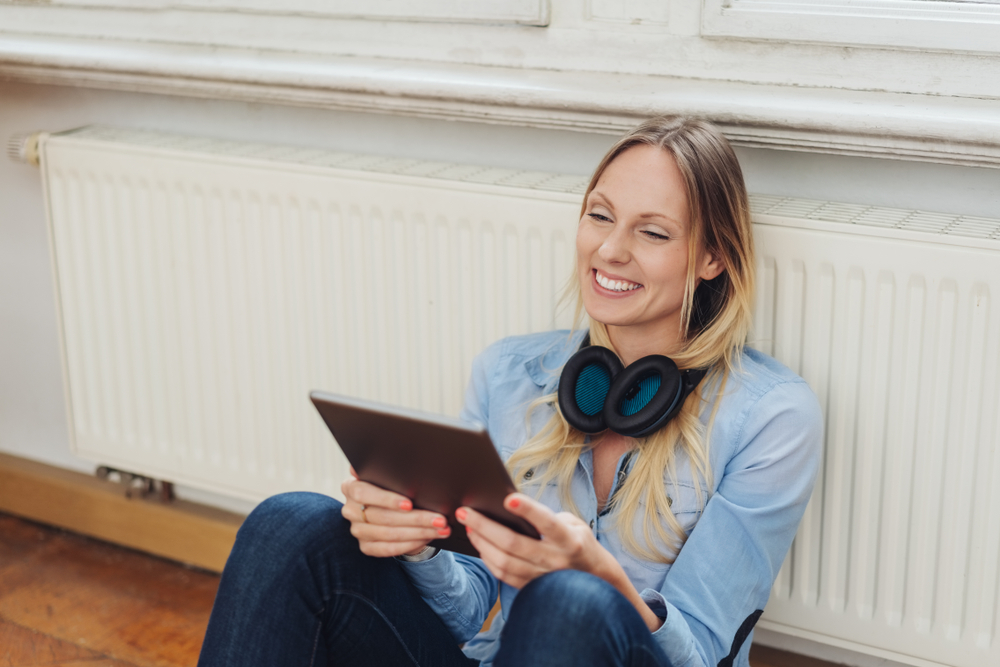 Happy,Young,Woman,Sat,Next,To,Radiator,At,Home,With
