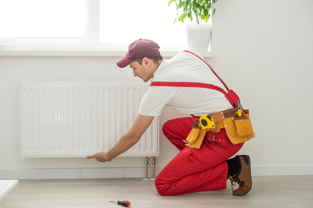 Man,In,Work,Overalls,Using,Wrench,While,Installing,Heating,Radiator